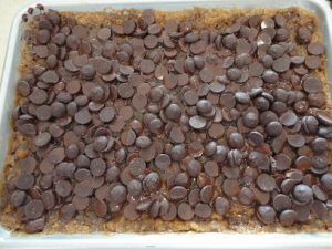 Photo of chocolate chips spread as the top layer for Chocolate Macadamia Nut Bars